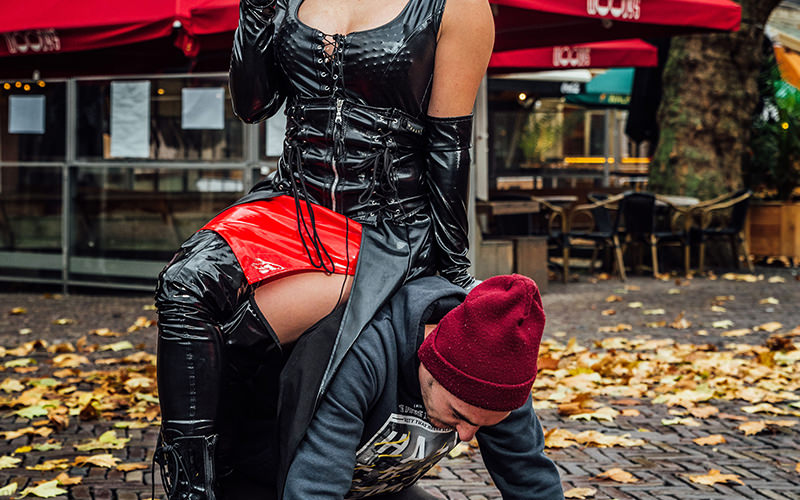 A woman in dominatrix gear sitting on the back of a man who is on all fours