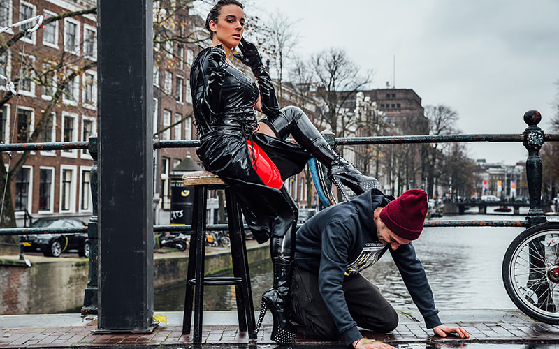 A woman in dominatrix gear sitting on a stool while resting her feet on the back of a man