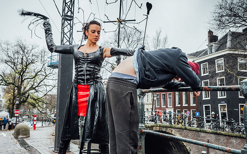 A woman in dominatrix gear whipping a man who is bent over