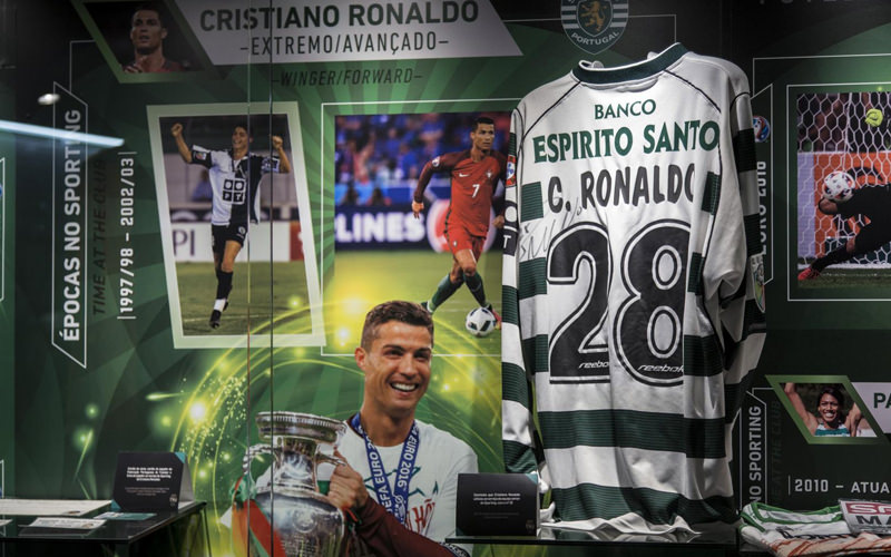 A football shirt with C.Ronaldo on the back and the number 28, with various photographs of Cristiano Ronaldo on display