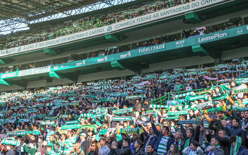 A group of Sporting Lisbon supporters in a crowd holding green scarves above their heads