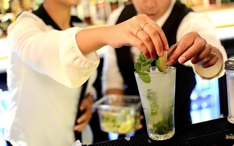 A man helping a woman make a cocktail