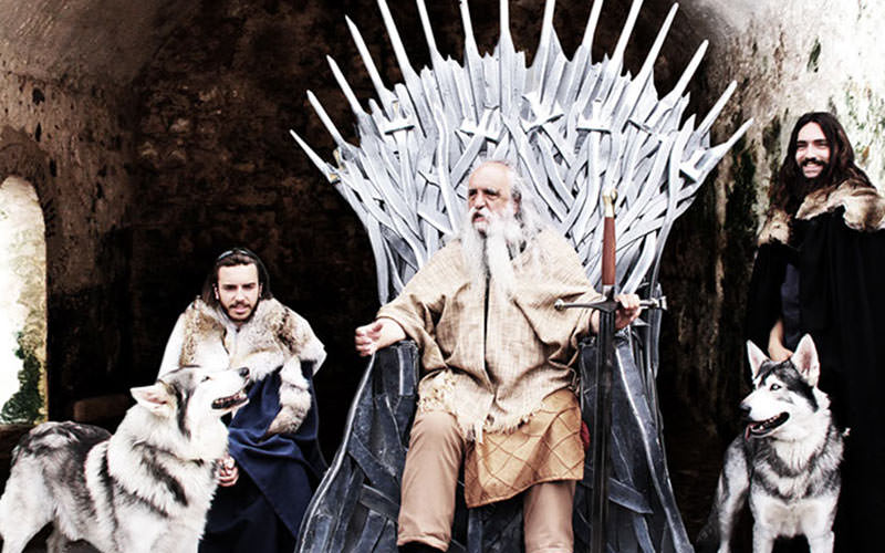 An old man in costume sat on the Iron Throne, with two men and two huskies beside him