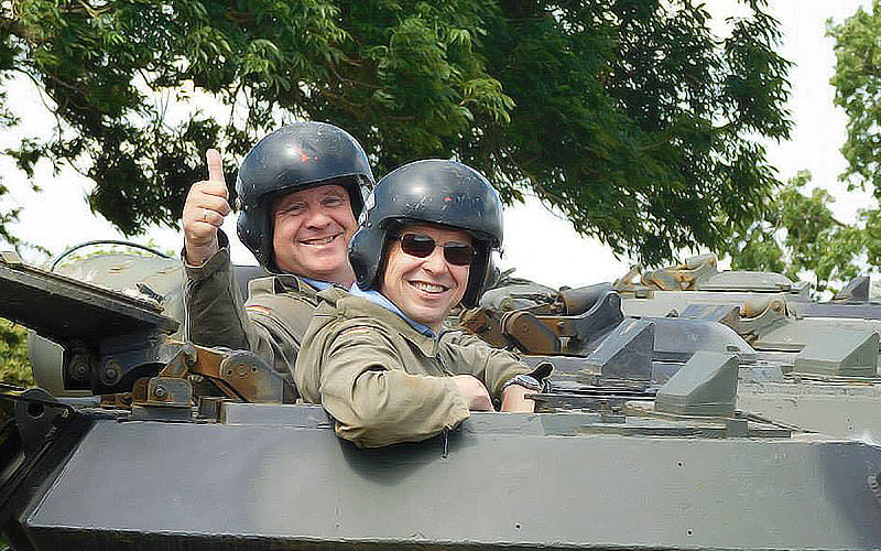 Two men smiling whilst driving a tank