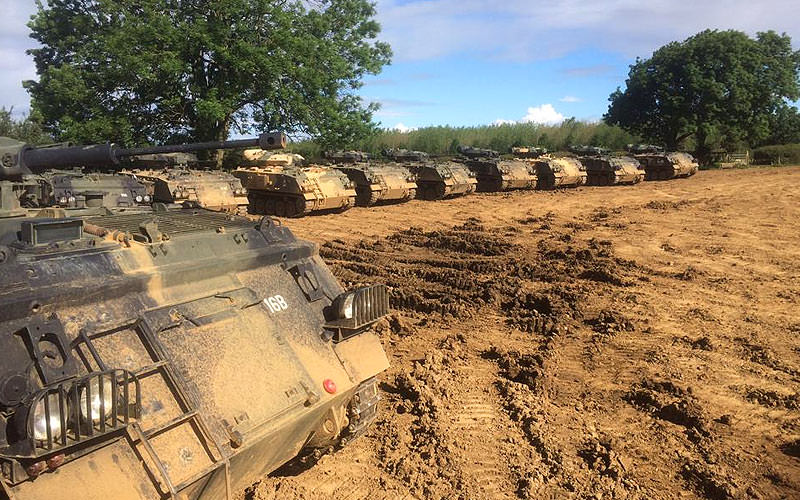 Many tanks lined up in a muddy field