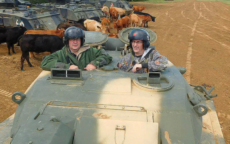 Men driving a tank with cows in the background