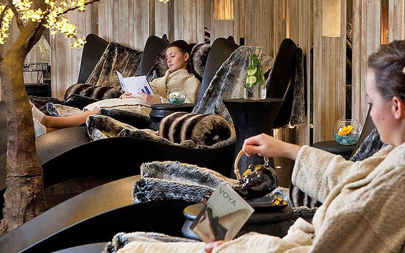 Two women relaxing in huge, comfortable armchairs