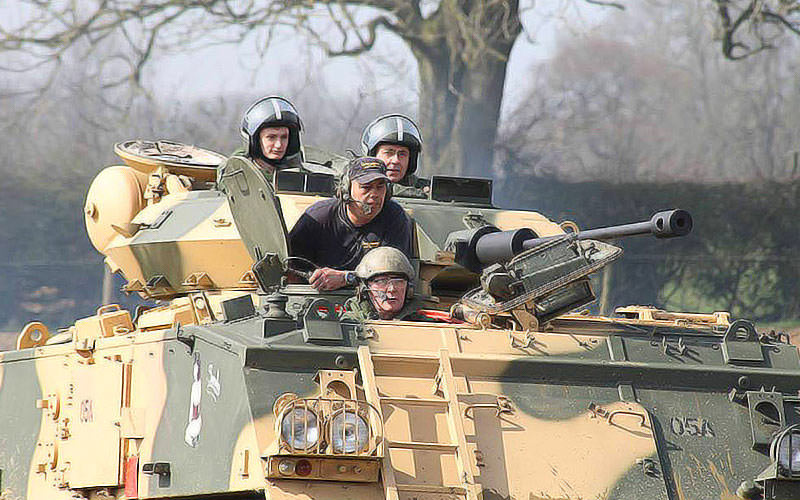 Some men driving a tank and wearing helmets