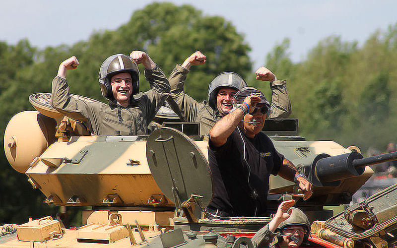 Men holding their arms up in celebration in a tank