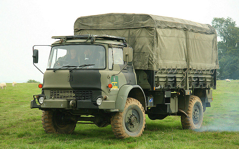 A camouflaged vehicle driving through a field