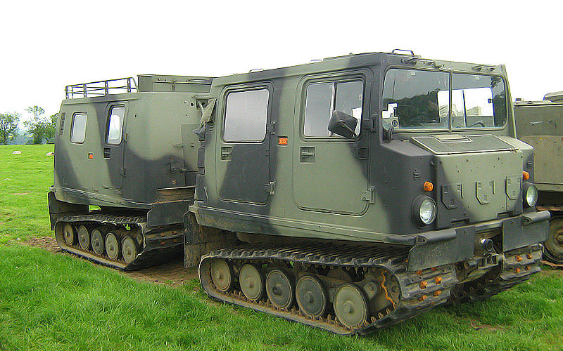 Two camouflaged vehicles in a field