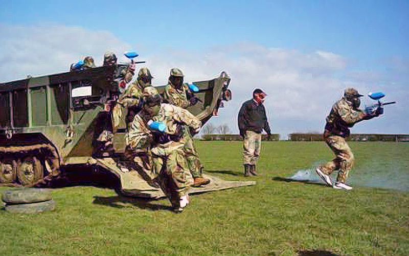 Men running out of a tank with paintball guns