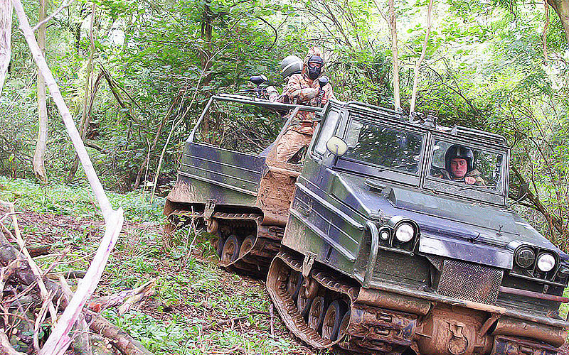 Men driving a tank through the woods