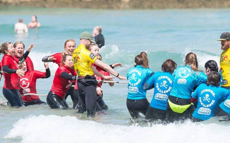 Two teams of women playing tug of war in the water