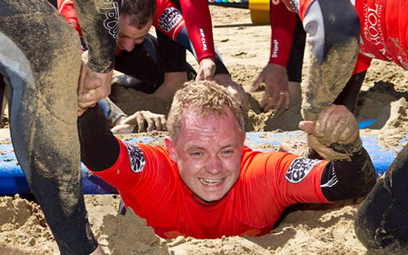 A man in the sand, with men helping him