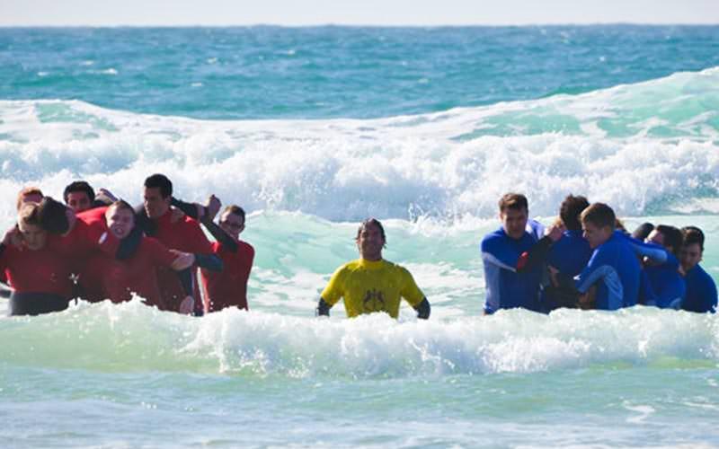 Two teams of men racing in the sea