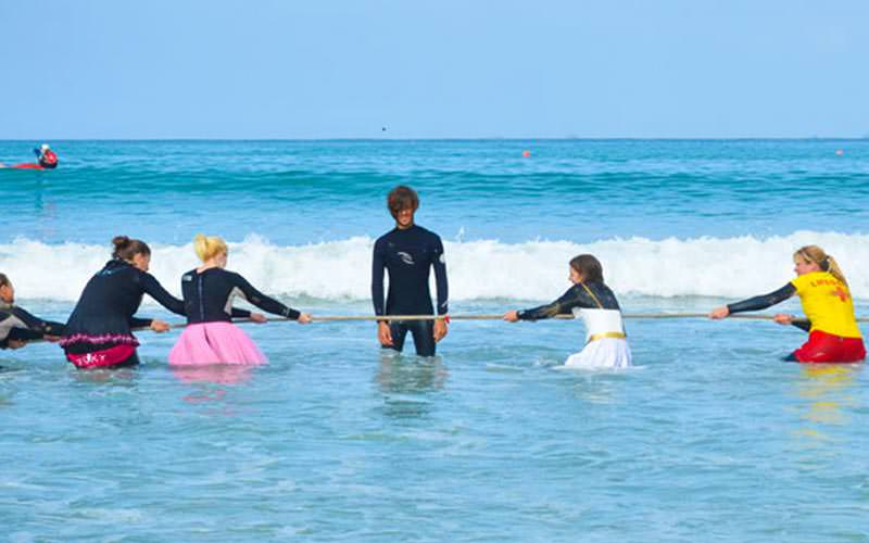 Women playing tug of war in the sea with an instructor in the middle