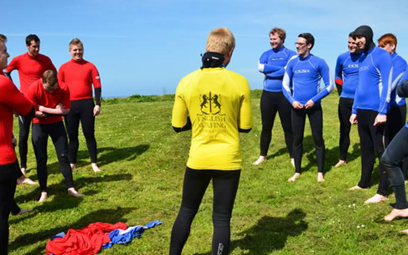 An instructor speaking to two teams of men in wetsuits