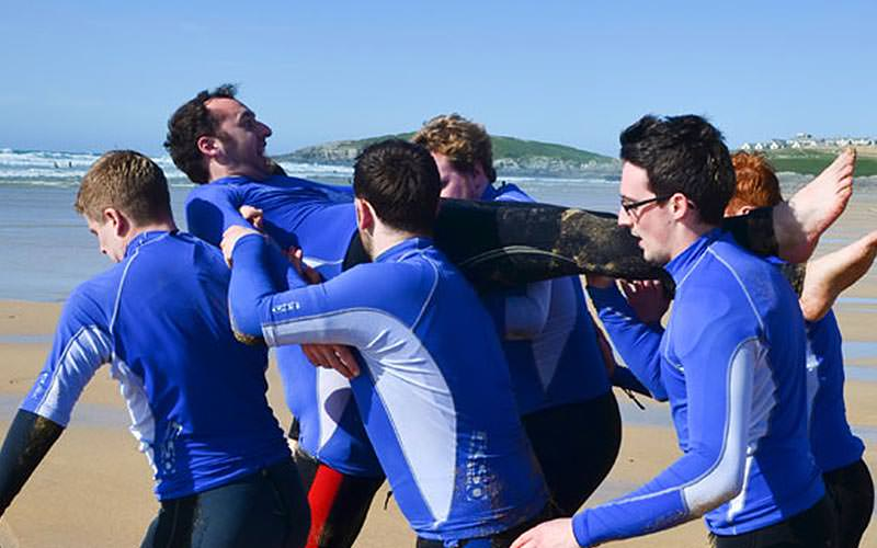 A group of men in wetsuits, carrying a man on their shoulders