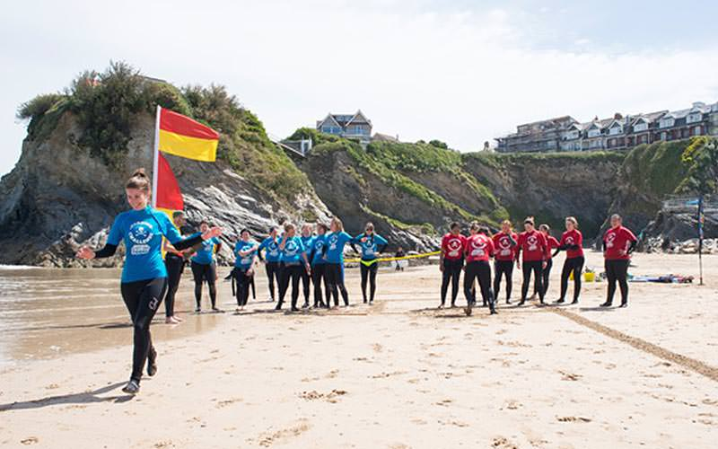 A woman running on the sand whilst two teams of women look on