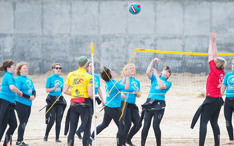 Two teams of women playing volleyball