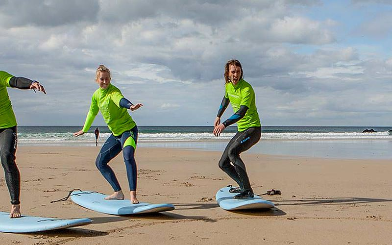 Three people receiving a surfing lesson on the beach