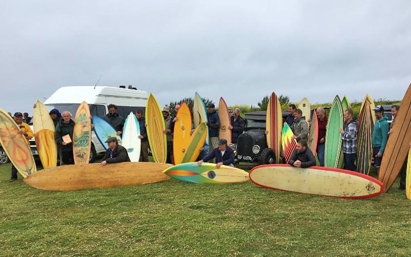 Lots of men in a field with wooden surfboards