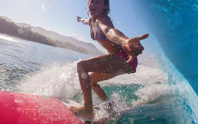 A girl surfing on a large wave