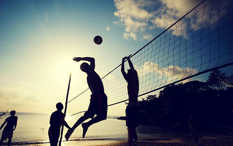 Four men's silhouettes as they play beach volleyball