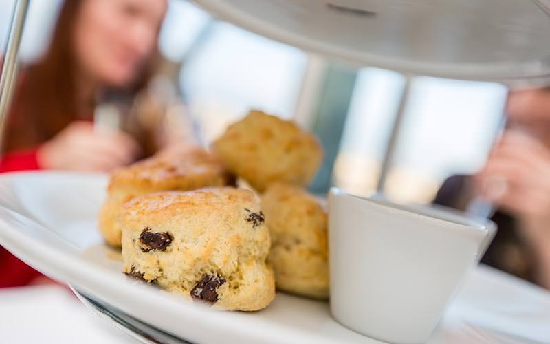 A close up of small scones on a cake stand with women in the background