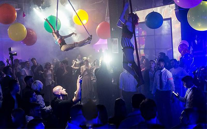 Baloons and trapeze artists above a packed dance floor