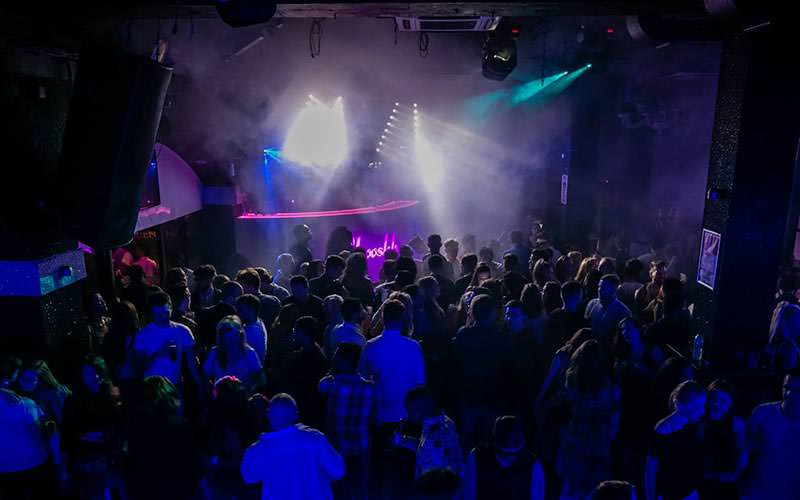 A packed dance floor to a backdrop of strobe lights and smoke