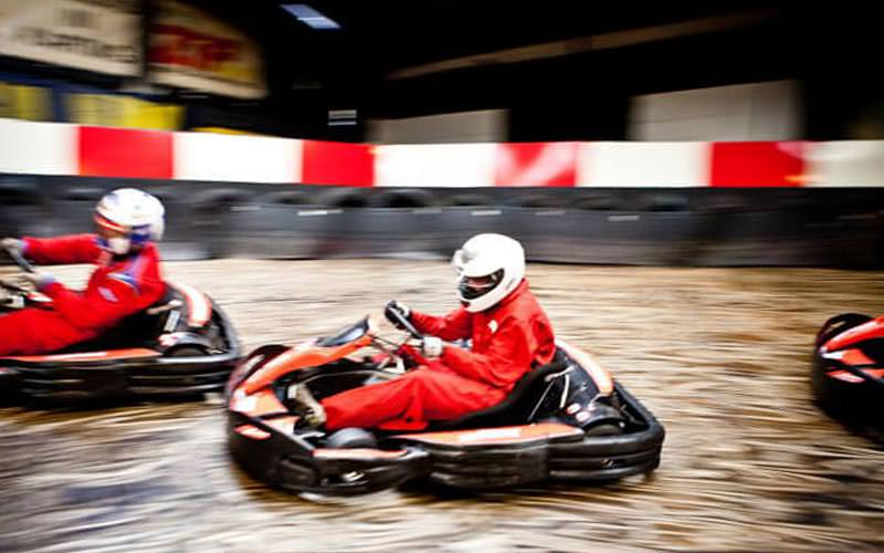 Go Karts travelling around an indoor track at speed