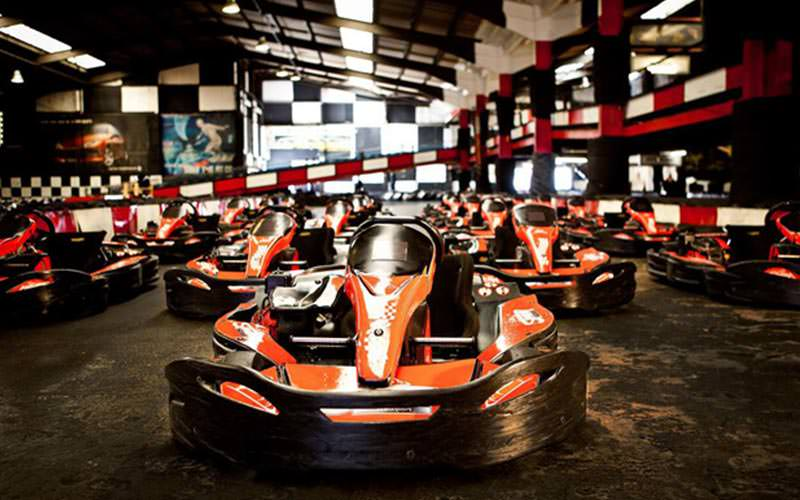 A line up of empty Go Karts on an indoor track