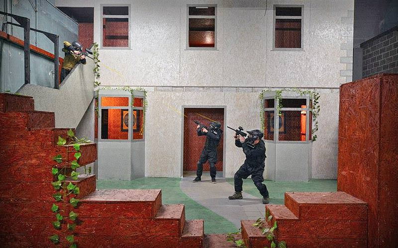 Three men firing paintballs at each other in an indoor game arena