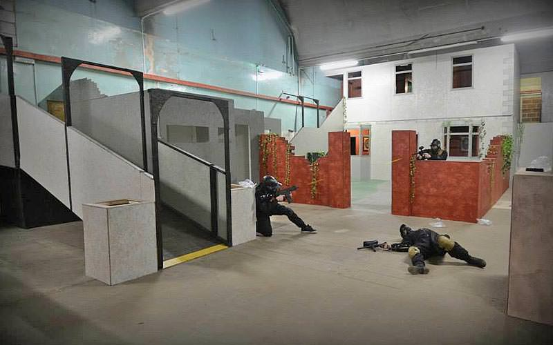 Two men firing paintballs at each other in an indoor game arena near another man lying on the floor