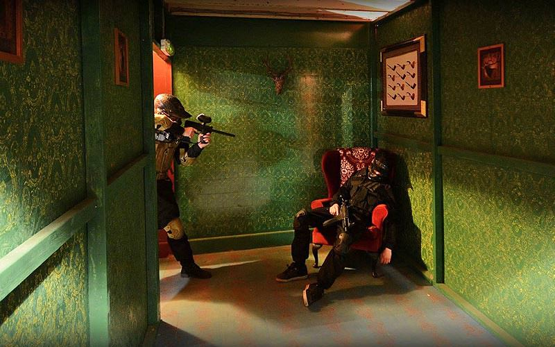 A man aiming a paintball marker at another man collapsed in red chair, in a green corridor