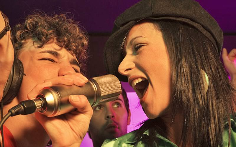 A man and woman singing into a microphone with people in the background