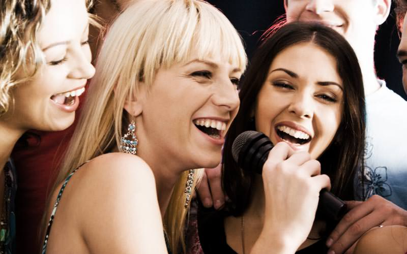 Three women singing into a microphone with people laughing in the background