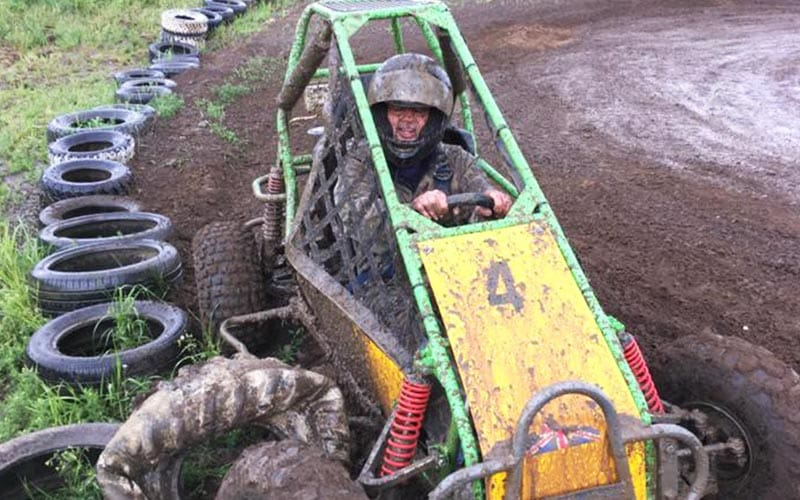 Man in yellow jump buggy sitting on edge of mud track alongside the tyre wall.