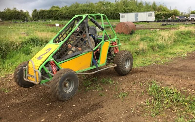 Jump Buggy lifting over a mound in the field.