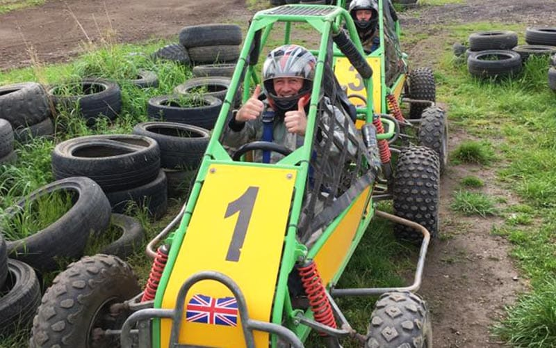 Two jump buggies lined up on narrow track in between tyre walls.