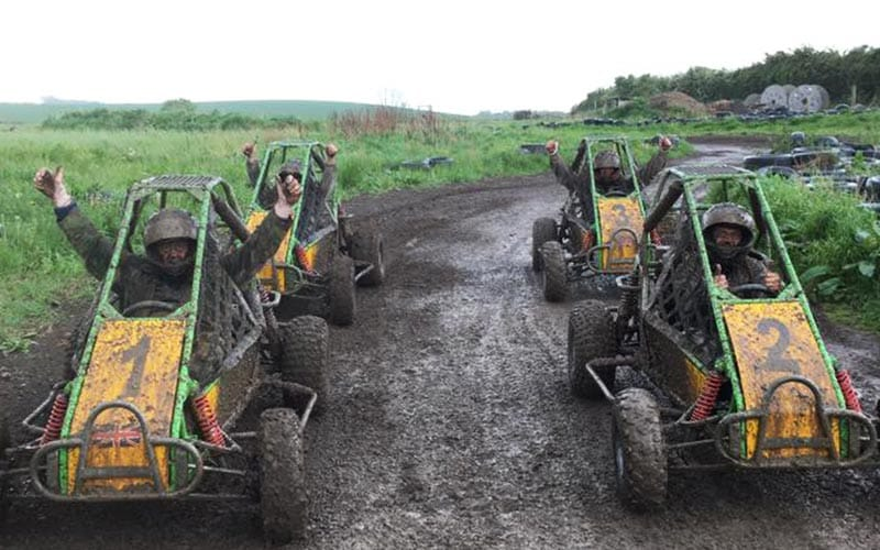 4 jump buggies lined up at start of race on a muddy track with drivers raising their hands up out of the buggies.