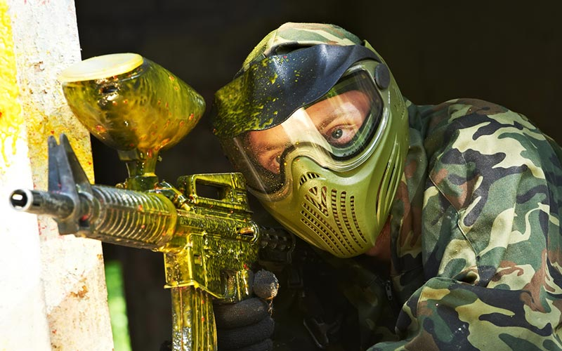 A person wearing a mask and holding a paintball gun