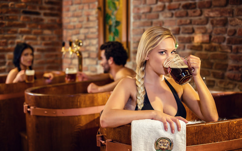 A woman drinking a pint of beer while in a spa tub