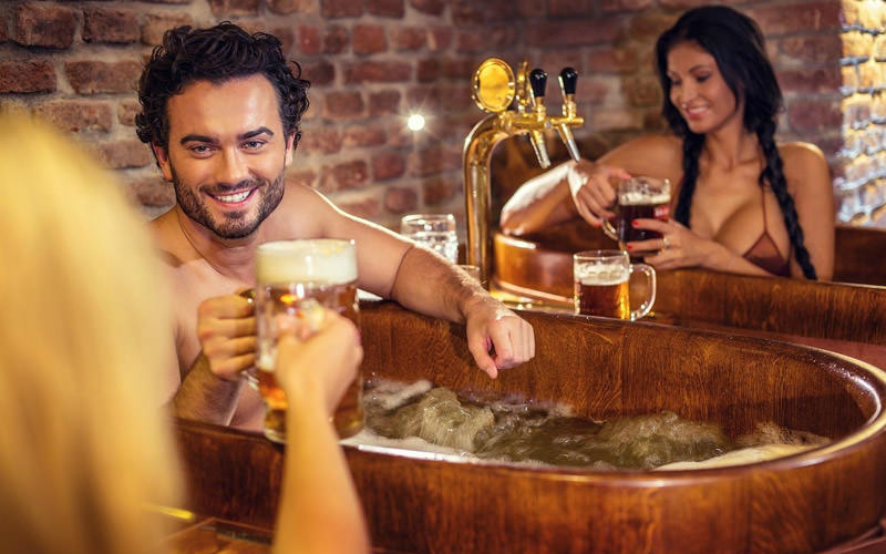 Two women and one man drinking beer in a spa tub