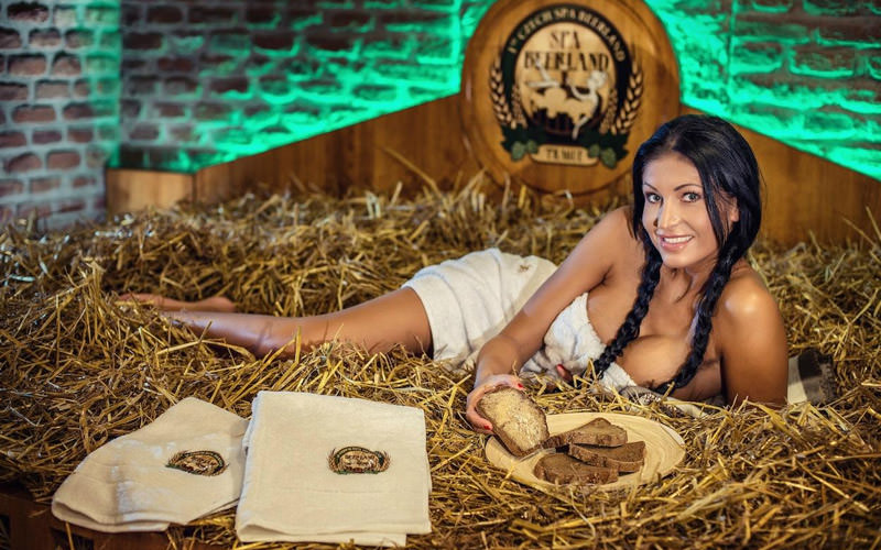 A woman lying on a bed of hay holding thickly cut bread