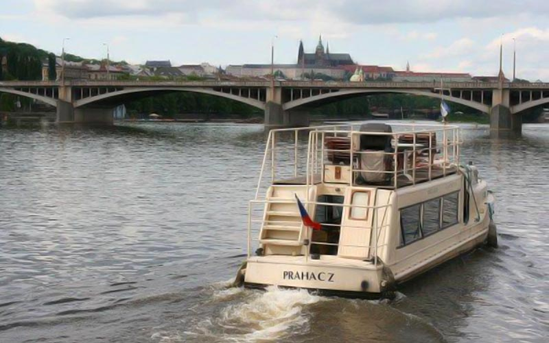 A boat floating down a river in Prague