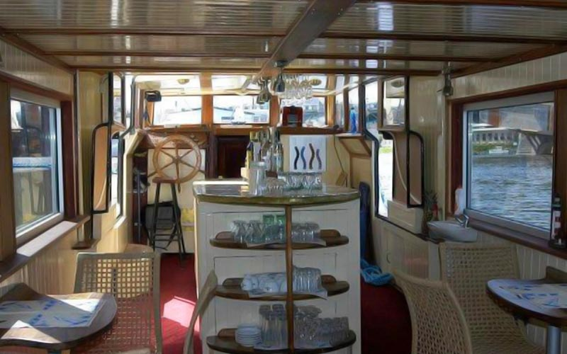 The inside of a boat with several tables and chairs, as well as a bar