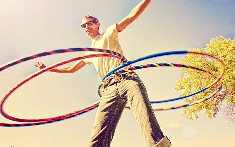 A man hula hooping with four hoops